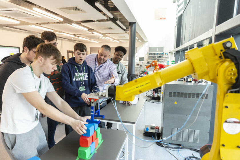 Engineering students and tutor with robotic arm Bedford College