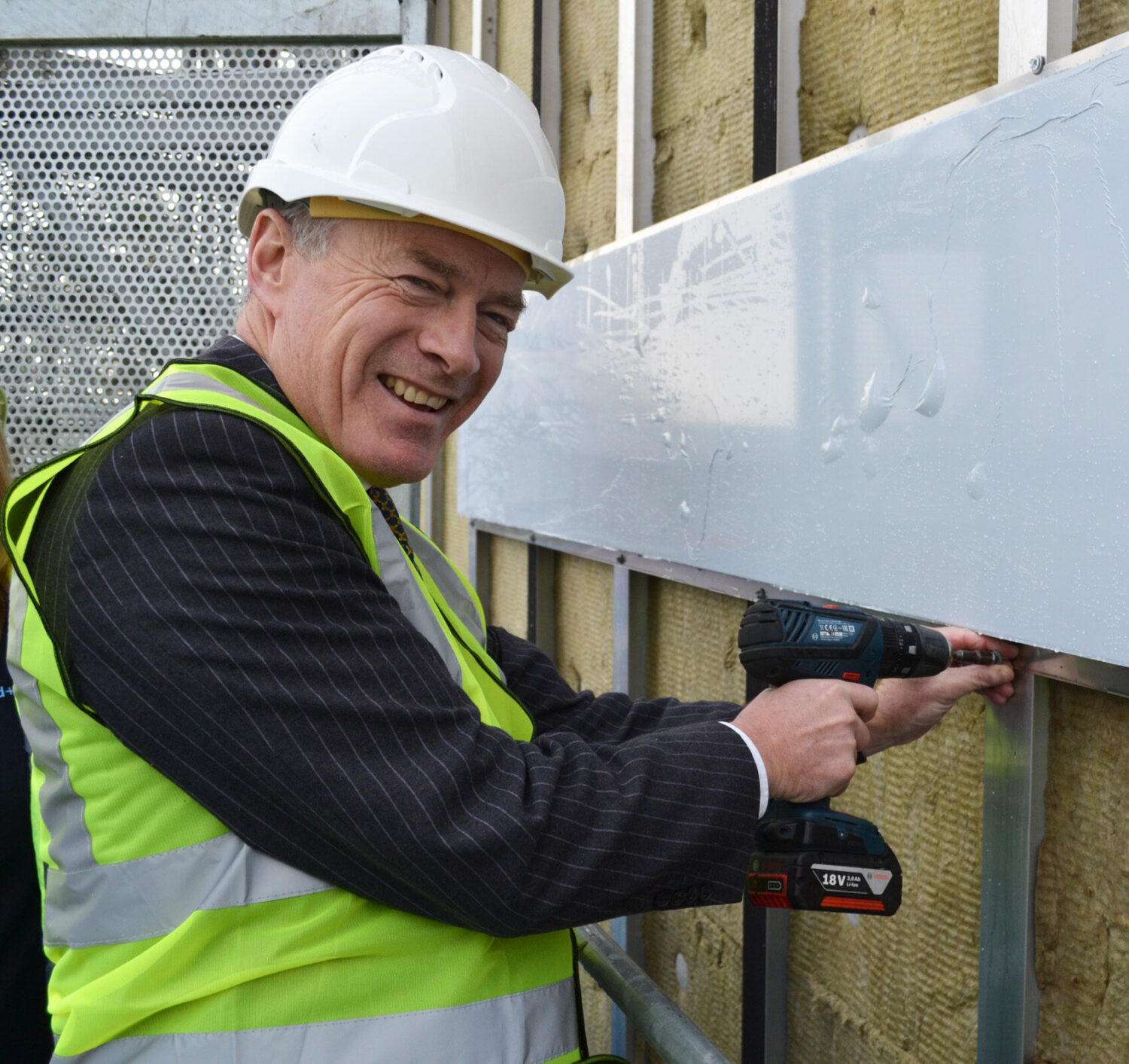 Ian Pryce putting on first cladding pannel at Wellingborough